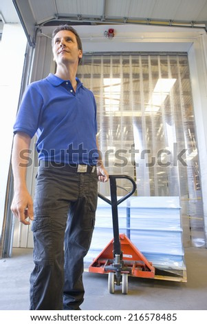 Worker pulling inventory on hand truck on loading dock - stock photo