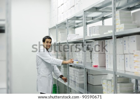 Worker putting boxes together on shelves in modern warehouse - stock photo