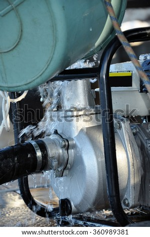 Worker refueling mobile water pump machine. Pump for pumping dirty water. Water pump. Old fire extinguishing system. Worker refueling mobile water pump. - stock photo