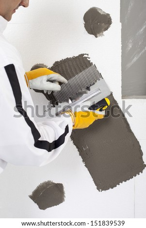 Worker reinforcing a window frame - stock photo