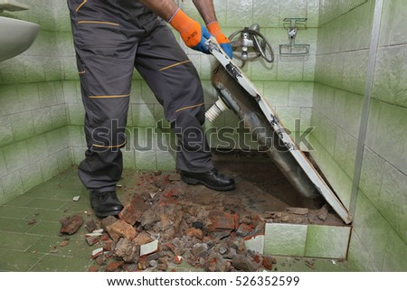 Worker remove, demolish old bathtub and tiles in a bathroom