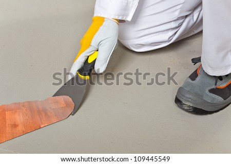 worker remove old carpet from floor with trowel - stock photo