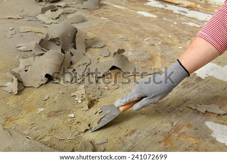 Worker removes glue and rubber with putty knife from floor - stock photo