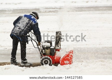 Worker removes snow with hand snowblower - stock photo