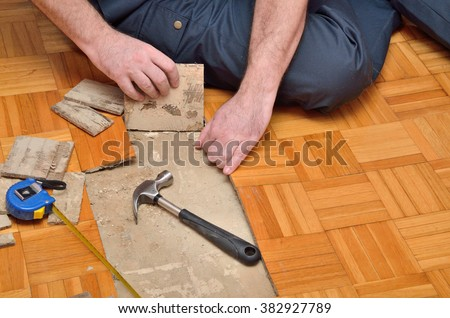 Worker removing pieces of parquet damaged by moisture or water - stock photo