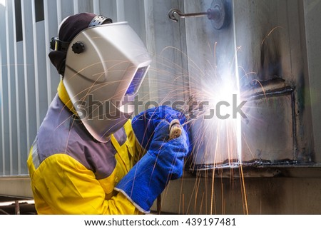 Worker repair the damage container wall, Industrial Worker at the factory welding closeup - stock photo