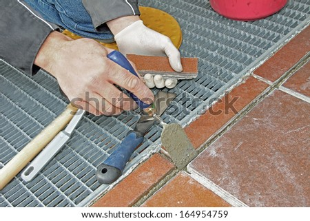 worker repairing and grouting patio outdoors - stock photo