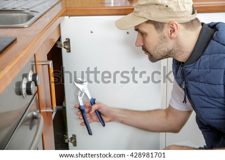 Worker repairing the sink in the kitchen. Man looks at the sink and holding a pipe wrench.