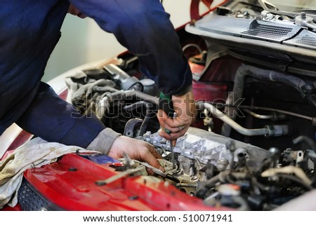Worker repairs a car in a car repair center
