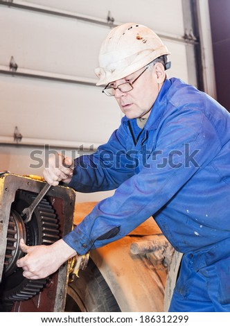 worker repairs transmission - stock photo