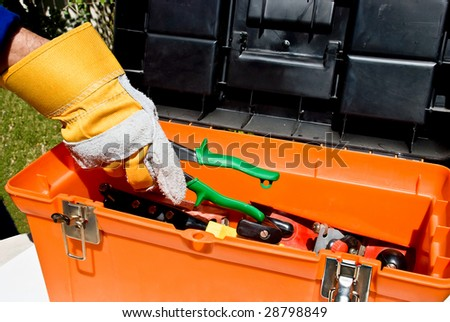 Worker's hand taking snips out of a toll box - stock photo