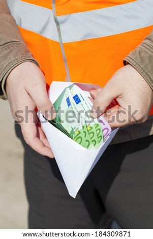 Worker's hands with euro banknotes in envelope - stock photo