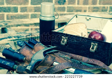 Worker's lunch break with lunch pail, beverage container, tool belt, tools, apple, sandwich, and napkin on wooden pallet with brick wall in background. Image has been cross processed. - stock photo