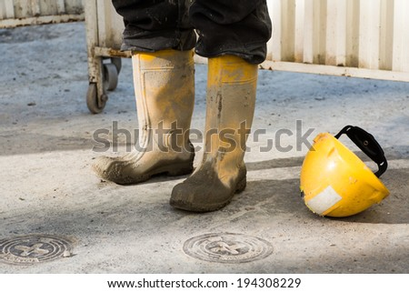 Worker's muddy boots and helmet,  worker taking a break - stock photo