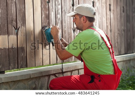 Worker sanding away old paint from a wooden fence using power tool