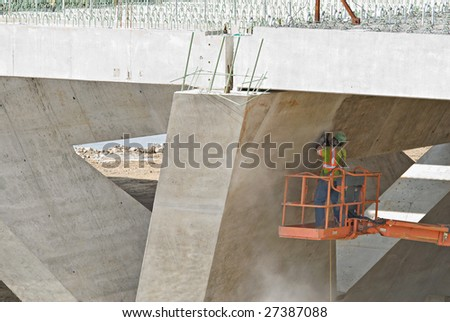Worker Sanding Under Bridge - stock photo