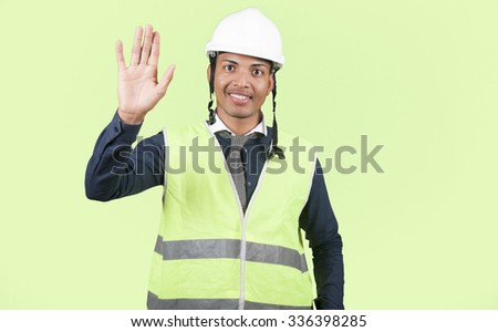 Worker saying hello on green background - stock photo