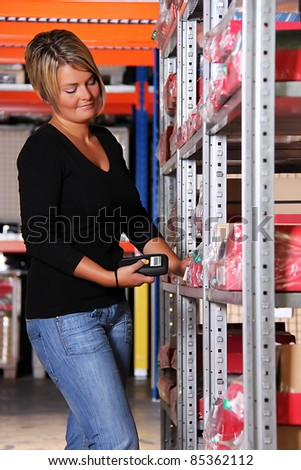 worker scans pallets and boxes in the warehouse - stock photo