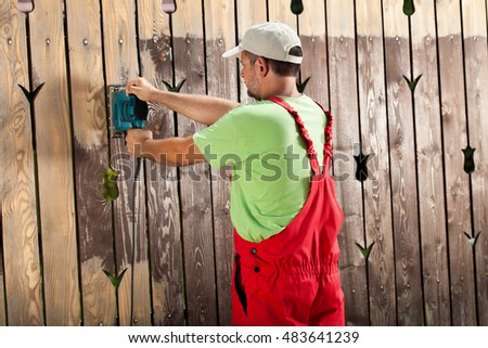 Worker scraping old cracked paint from wooden fence with power tool - a vibrating sander
