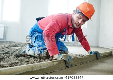 worker screeding indoor cement floor with screed  - stock photo