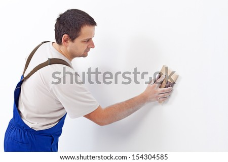Worker scrubbing the wall with sandpaper - preparing the surface for painting - stock photo