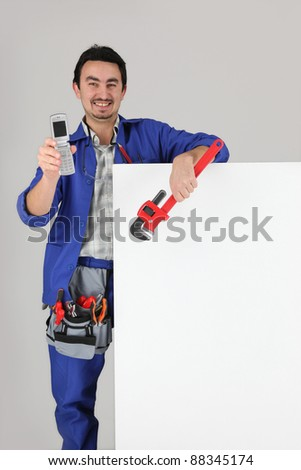 Worker showing off his cellphone - stock photo