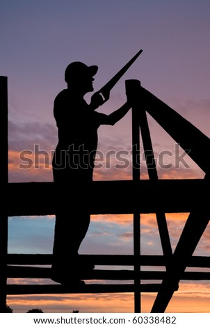 worker silhouette at roofing works over scenic dawn or sunset - stock photo