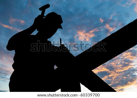 worker silhouette with hammer at roofing works over scenic dawn or sunset - stock photo
