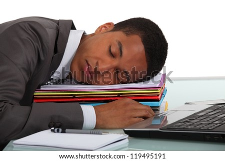 Worker sleeping on a stack of folders - stock photo