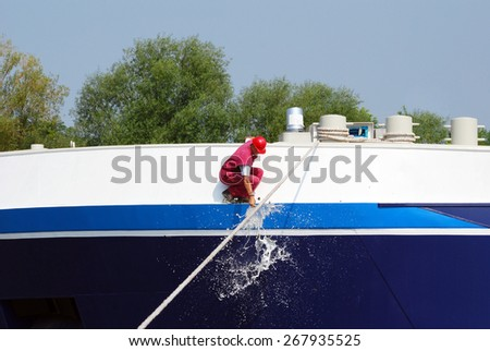 worker smashing a bottle of champagne on the new ship  - stock photo