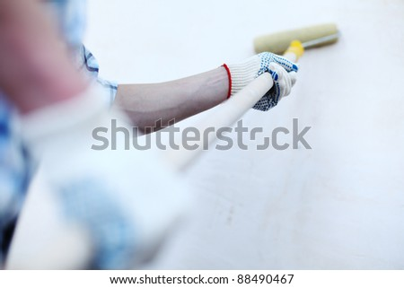 worker spends anchor roller on the wall - stock photo