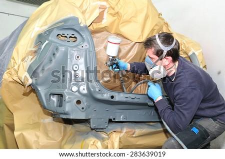 Worker spraying gray base coat. - stock photo