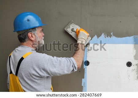 Worker spreading  mortar over styrofoam insulation and mesh  with trowel - stock photo