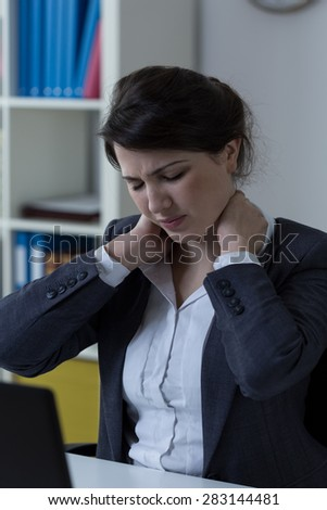 Worker suffering from neck ache at office - stock photo