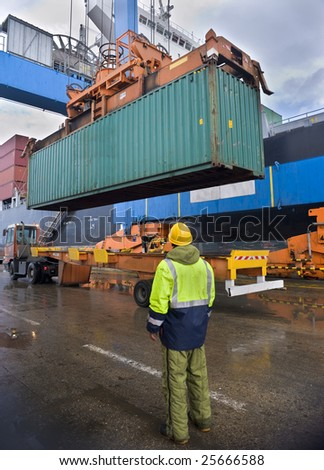 worker supervising container uploading at dock - stock photo