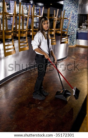 Worker sweeping floor of closed restaurant - stock photo