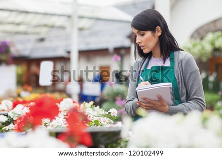 Worker taking notes while choosing a flower in the garden centre - stock photo