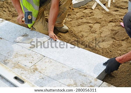 Worker tapping paver into place with rubber mallet. Installation of granite paver blocks series with motion blur on hammers and hands. - stock photo