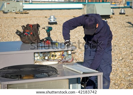 Worker testing a roof top air exchange units operation. - stock photo
