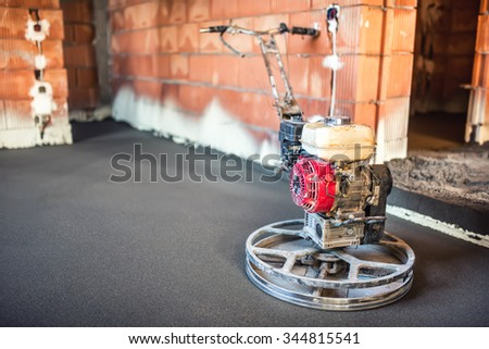worker trowelling with power tool on concrete surface at new house construction site - stock photo