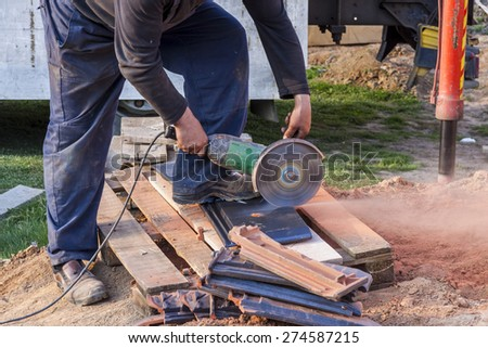 Worker using a hand circular saw to cut a roof-tile - stock photo