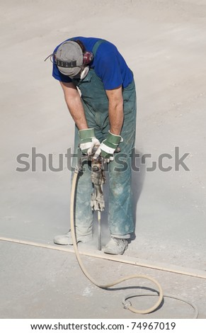 Worker using a handheld hydraulic hammer - stock photo