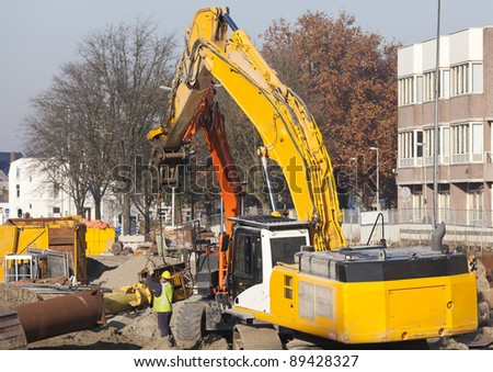 Worker using a spanner to tighten a nut on a metal tube hoisted by two excavators - stock photo