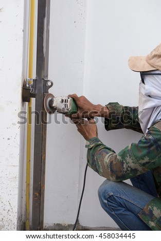 worker using an angle grinder to grinding metal