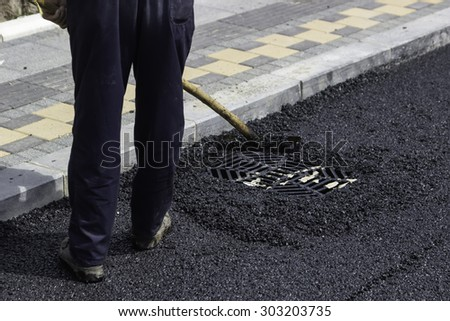 Worker using asphalt lute to level the asphalt and prepare it for compaction. Selective focus and some motion blur present.