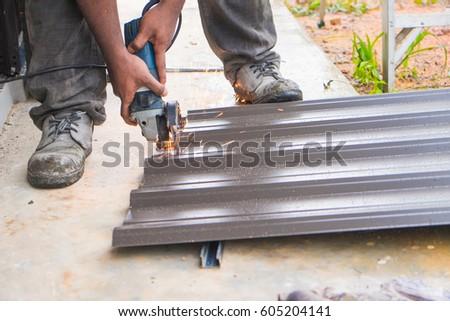Worker Using Grinder Machine To Cut Metal Roof
