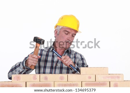 Worker using hammer and chisel on wall - stock photo
