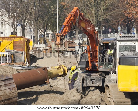Worker using spanner and hammer to tighten a nut on a steel tube hoisted by a excavator - stock photo