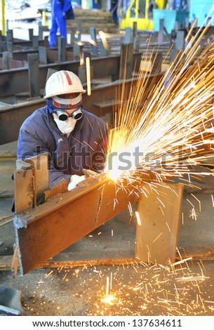 worker using torch cutter to cut through metal in factory - stock photo