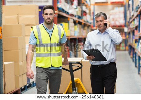 Worker walking with his manager over the phone in warehouse - stock photo
